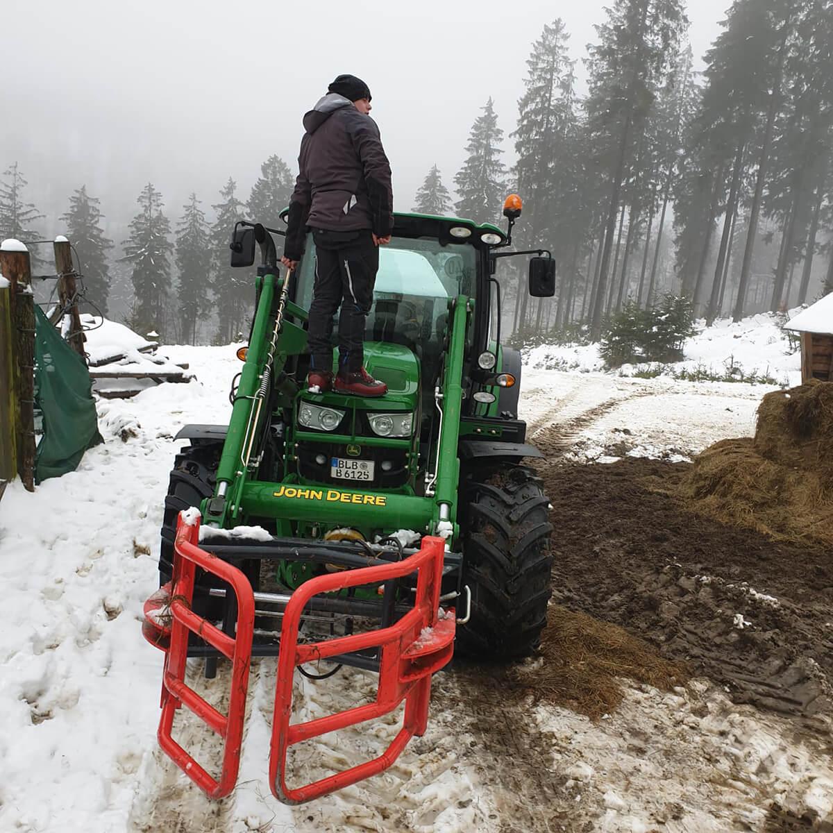 Wisent-Ranger steht auf dem Traktor in der verschneiten Wisent-Wildnis um sich einen Überblick zu verschaffen